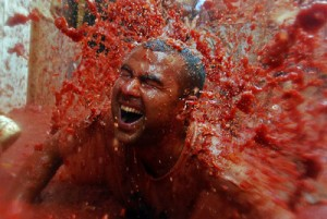 Un participante recibe una explosión de zumo de tomate sobre su cuerpo durante la fiesta de la Tomatina de Buñol. / HEINO KALIS (REUTERS)